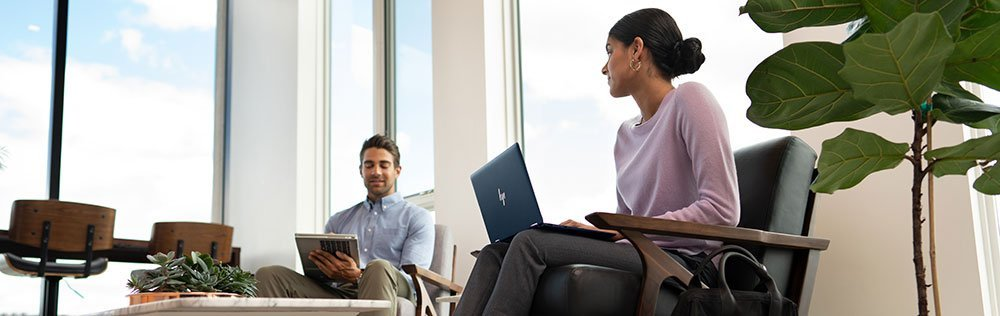 Business man and woman discussing work with HP laptops